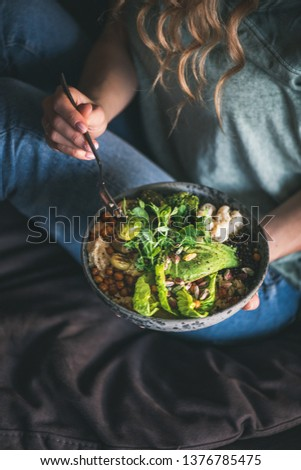 Healthy dinner or lunch. Curly woman in t-shirt and jeans sitting and eating vegan superbowl or Buddha bowl with hummus, vegetable, fresh salad, beans, couscous and avocado. Clean eating food concept
