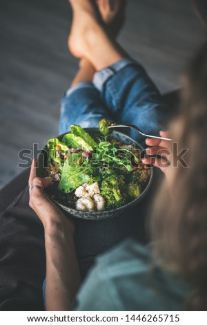 Healthy dinner or lunch. Curly woman in t-shirt and jeans sitting at home and eating vegan superbowl or Buddha bowl with hummus, vegetable, fresh salad, beans, couscous and avocado, top view