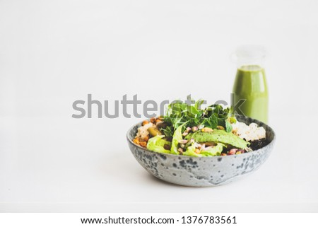 Healthy dinner or lunch. Vegan superbowl or Buddha bowl with homemade hummus, vegetable, fresh salad, beans, couscous and avocado and green smoothie in bottle over white background, copy space