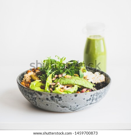 Healthy dinner or lunch. Vegan superbowl or Buddha bowl with hummus, vegetable, fresh salad, beans, couscous and avocado and green smoothie in bottle over white background, copy space, square crop