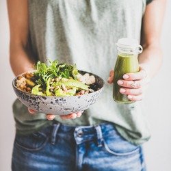 Healthy dinner or lunch. Woman in t-shirt and jeans standing and holding vegan superbowl or Buddha bowl with hummus, vegetable, salad, beans, couscous and avocado and smoothie in hands, square crop