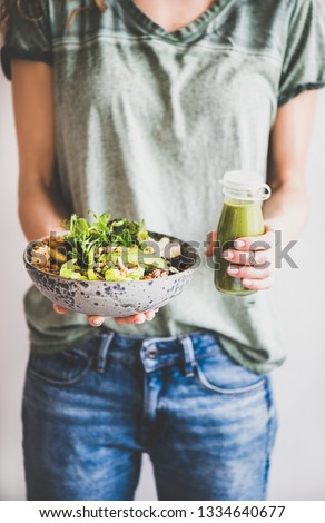 Healthy dinner or lunch. Woman in t-shirt and jeans standing and holding vegan superbowl or Buddha bowl with hummus, vegetable, fresh salad, beans, couscous and avocado and smoothie in hands