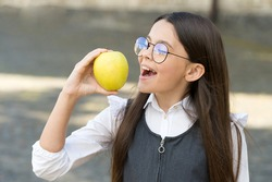 Healthy dose of vitamin C. Happy kid eat apple outdoors. School snack. Vitamin nutrition. Health education. Eating right carbs. Natural vitamin food. Energy diet. Give hoot, eat more fruit.