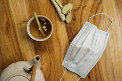 healthy drink from lemongrass and ginger with face mask on the wooden table
