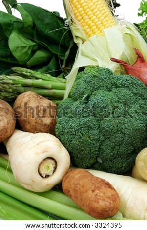 Healthy eating ~ a variety of fresh vegetables, including sweetcorn, spinach, lettuce, broccoli, parsnip, kipfler potatoes, celery, shallots, asparagus. - stock photo