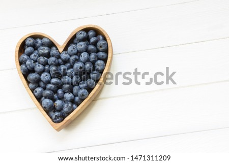 Healthy eating and nutrition.Blueberries in wooden plate(heart shape) on white wooden background.Love fruits and berries,healthy eating, healthy breakfast, vegan food,diet food,nature meal