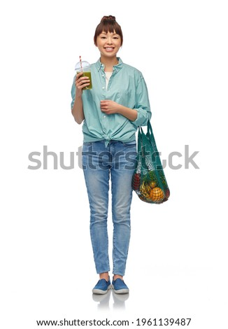 healthy eating and sustainability concept - asian woman drinking green smoothie from plastic cup and holding reusable string bag with fruits and vegetables over white background Stock photo ©