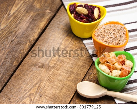 Healthy eating background. Wooden spoon and ceramic cups filled with wheat bran, mixtures of nuts with dried fruits and berries. Peeled hazelnut, almond, papaya, cranberries