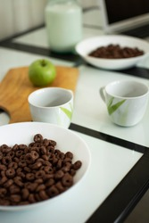 healthy eating. bar menu. a plate of cereal, two white mugs. green apple on a cutting board, another plate of cereals, milk in a can, part of a laptop in blur. on a black and white glass table.