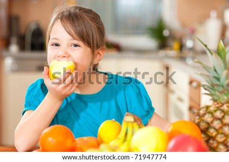 Healthy eating child eating an apple lots of fresh fruit on the table in front