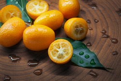 Healthy eating concept: Bunch of delicious wet fresh kumquats on wooden background. Organic food with full of vitamins.  Water drops on orange kumquats and green leaves.