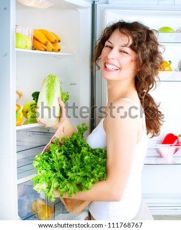 Healthy Eating Concept .Diet. Beautiful Young Woman near the Refrigerator with healthy food. Fruits and Vegetables in a Fridge - stock photo
