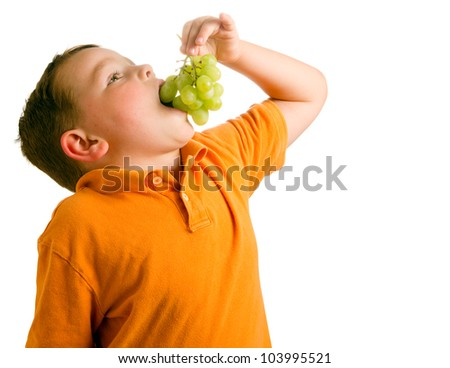Healthy eating concept with child eating grapes isolated on white