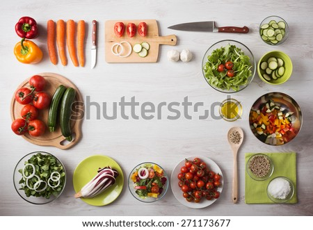 Healthy eating concept with fresh vegetables and salad bowls on kitchen wooden worktop, copy space at center, top view