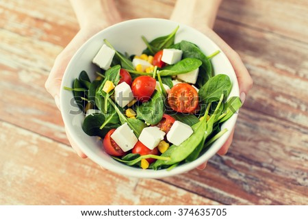 healthy eating, dieting and people concept - close up of young woman hands showing salad bowl at home