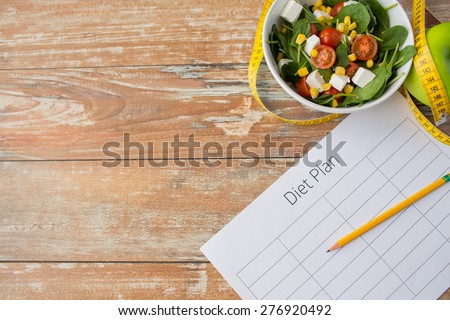 healthy eating, dieting, slimming and weigh loss concept - close up of diet plan paper green apple, measuring tape and salad #276920492
