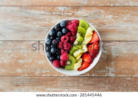healthy eating, dieting, vegetarian food and people concept - close up of fruits and berries in bowl on wooden table Stock photo ©