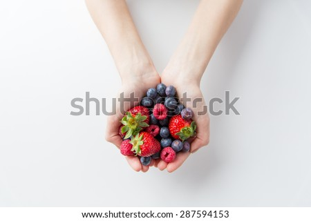 healthy eating, dieting, vegetarian food and people concept - close up of woman hands holding berries at home #287594153