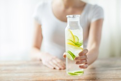 healthy eating, drinks, diet, detox and people concept - close up of woman with fruit infused water in glass bottle