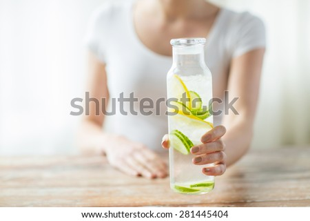 healthy eating, drinks, diet, detox and people concept - close up of woman with fruit water in glass bottle #281445404