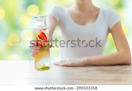 healthy eating, drinks, diet, detox and people concept - close up of woman with fruit water in glass bottle over green lights background