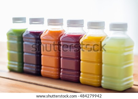 healthy eating, drinks, dieting and packaging concept - plastic bottles with different fruit or vegetable juices on wooden table #484279942