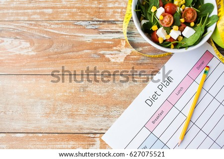 healthy eating, food, slimming and weigh loss concept - close up of diet plan paper with measuring tape and salad #627075521