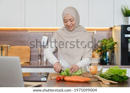 Healthy eating habits, mature muslim islamic wife woman in hijab cooking preparing vegetable salad using laptop as a tutorial for recipes online. Vegan vegetarian food Stock photo ©
