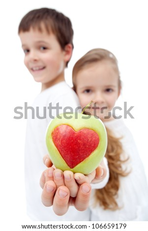Healthy eating kids concept - children holding apple with heart sign