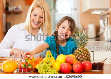 Healthy eating - mother and child sitting in the kitchen with different kinds of fruits for breakfast food - stock photo