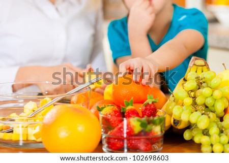 Healthy eating - mother and child sitting in the kitchen with different kinds of fruits for breakfast food