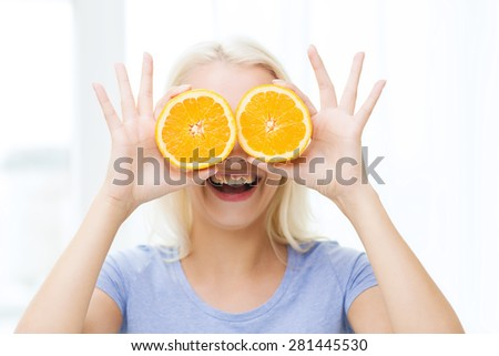 healthy eating, organic food, fruit diet, comic and people concept - happy woman having fun and covering her eyes with orange slices