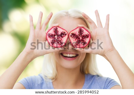 healthy eating, organic food, fruit diet, comic and people concept - happy woman having fun and covering her eyes with pomegranate over green natural background