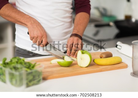 healthy eating, vegetarian food, diet and people concept - man with chopping fruits and cooking at home kitchen