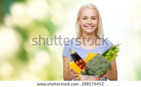 healthy eating, vegetarian food, dieting and people concept - smiling young woman with bowl of vegetables over green natural background