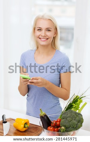 healthy eating, vegetarian food, dieting and people concept - smiling young woman with smartphone cooking vegetables at home