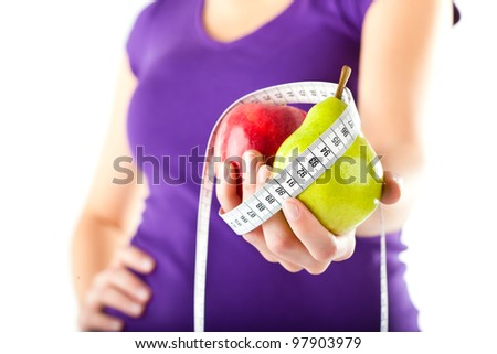 Healthy eating - woman with apple and pear and measuring tape