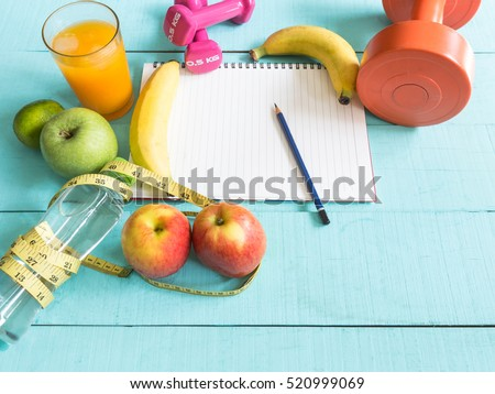 Healthy eating ,Workout and fitness dieting ,fitness and weight loss concept, tape measure, banana, apple, fruit and water bottle, blank copy space notebook,on wooden background