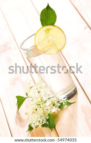 Healthy elder flower juice with lemon on wooden background.