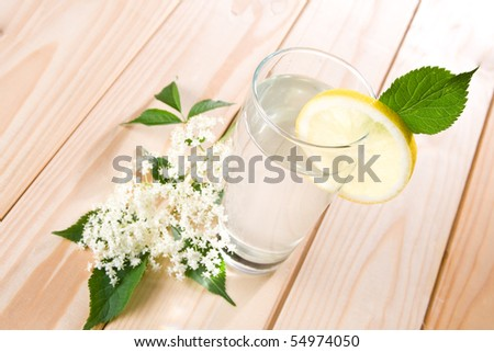 Healthy elder flower juice with lemon on wooden background.