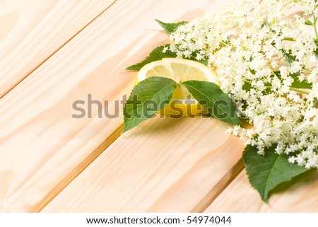 Healthy elder flower with lemon on wooden background.