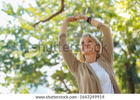 Healthy elderly woman do stretching and relaxing feel refresh and freedom in the park, healthy lifestyle and relax  concept.