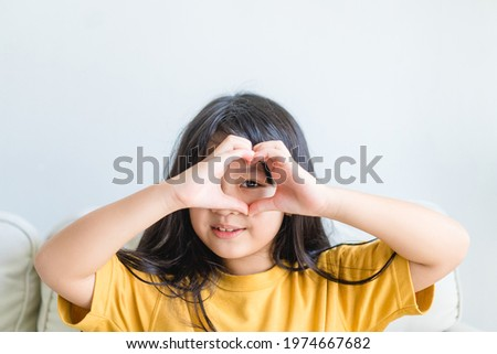 Healthy eyes and vision.Portrait happy asian kid child holding heart shaped hands on eyes.Smiling Girl With Healthy Skin Showing Love Sign. Eye care.Carotene vitamin.Focus, optician doctor, optical.