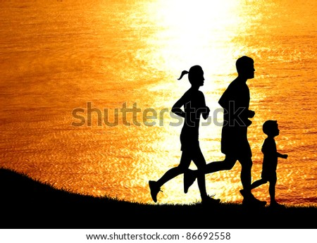 healthy family runner running together alongside the beach at  sunset silhouetted