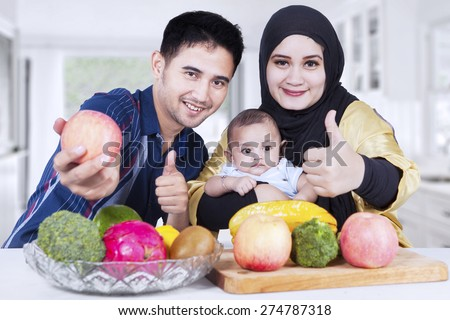 Healthy family showing thumbs-up in the kitchen with fresh fruits on the table