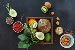Healthy farmer organic food in wooden box: fruit, vegetables, seeds, superfood, leaf vegetable on black background. Clean eating selection concept