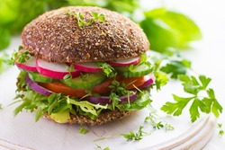 Healthy fast food. Vegan rye burger with fresh vegetables on white wooden  background