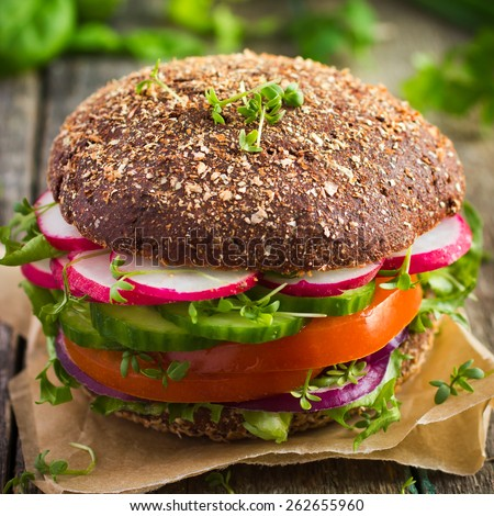 Healthy fast food. Vegan rye burger with fresh vegetables on wooden  background