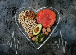 Healthy fats for heart on dark stone background. Concept.