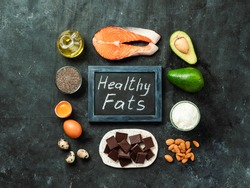 Healthy fats sources concept. Different food ingredients and chalkboard with ealthy Fats words on dark background. Top view or flat lay.